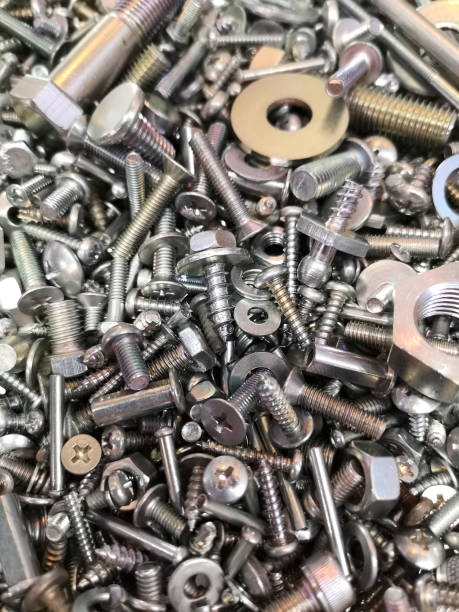 A big and interesting pile of new and shiny metal nuts and bolts, screws and washers. A big and interesting pile of new and shiny nuts and bolts, screws and washers of various metals, displayed for their high quality and workmanship, at a trade show. washer fastener stock pictures, royalty-free photos & images