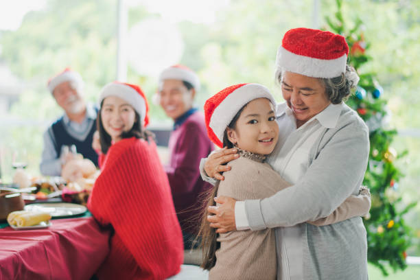 big asian family celebration in christmas day, grandmother hug and looking at granddaughter in front of meal table of family which smiling and felling happy at home. merry xmas and happy new year. - young girl computer home front imagens e fotografias de stock