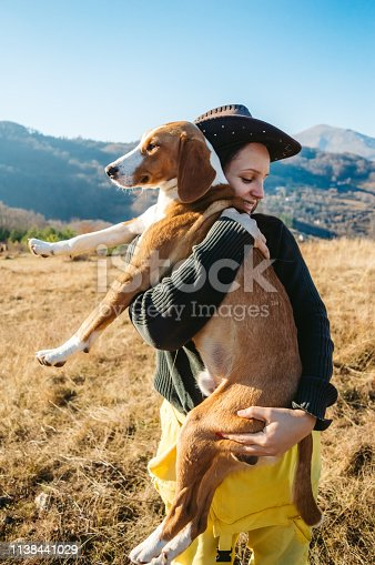 Young caucasian woman holding grown dog as a baby.