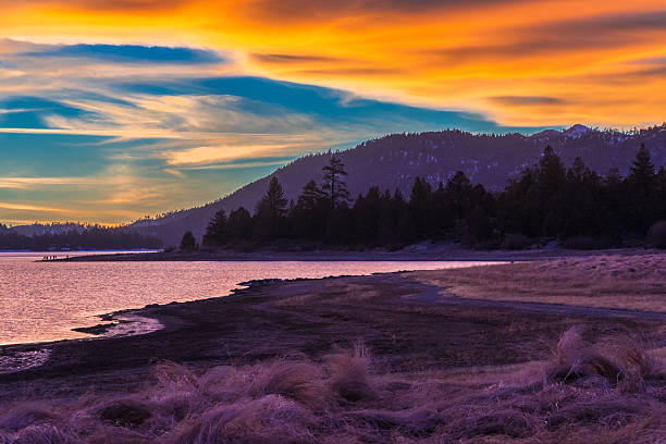 Big Bear Lake romantic sunset,reflections,cloudscape,CA (P) A sandy shoreline with backlit reeds fills the foreground leading back to the calm waters and reflections in Big Bear Lake against a dramatic cloudscape, Southern California san bernardino california stock pictures, royalty-free photos & images