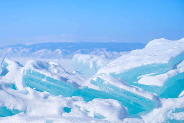 Big Beautiful blue ice on the Frozen Lake Baikal with mountains on the background. stock photo