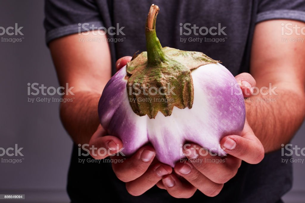 Big beautiful eggplant in man's hands. Healthy lifestyle. stock photo