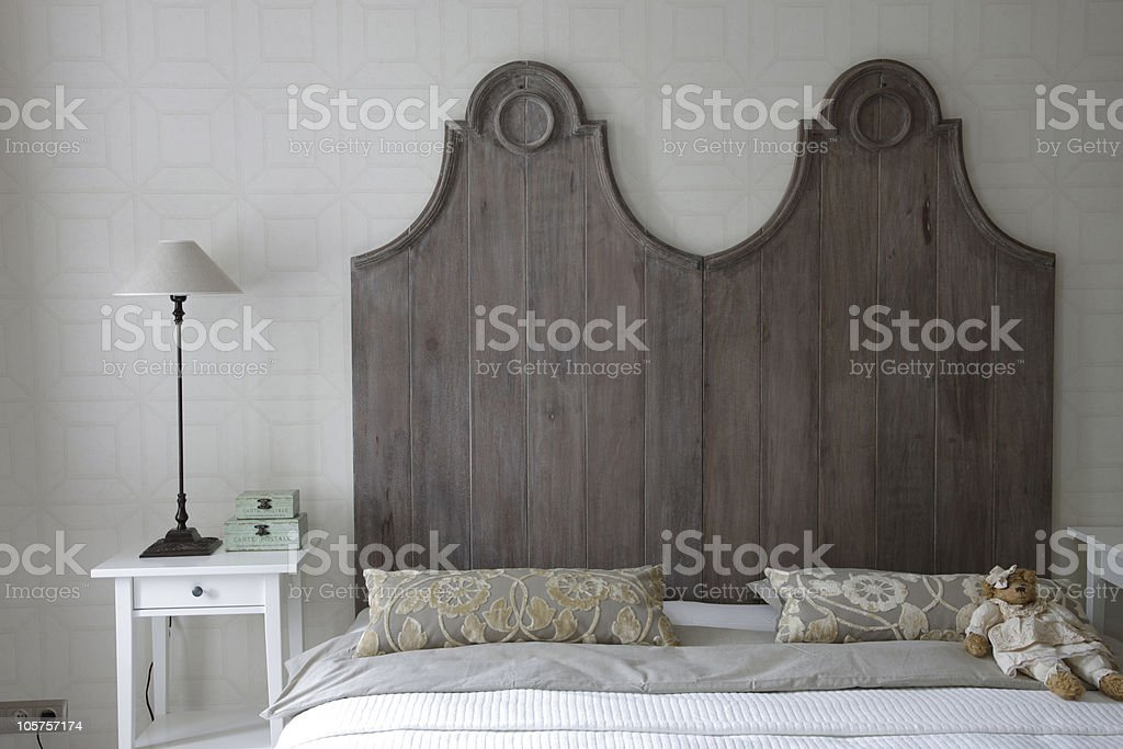 big bed with high headboard in gray color stock photo