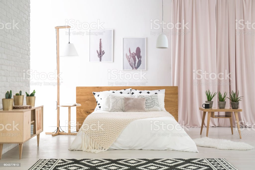 Big bed with white beddings in natural, wooden bedroom