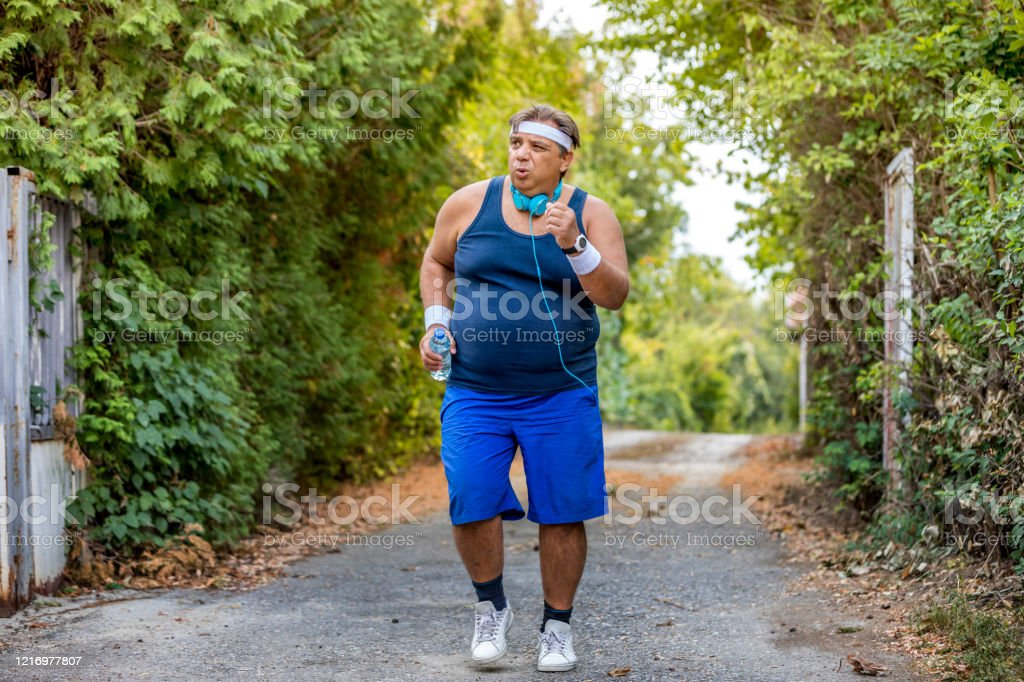 Big Belly Man Jogging Exercising Doing Cardio In The Park Slightly Overweight Loosing Weight Stock Photo Download Image Now Istock