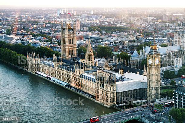 Aerial view of the the Elizabeth Tower which contains the bell Big Ben and the Houses of Parliament for the UK along the Thames River at dusk
