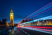 Big Ben at night and Westminster bridge with red and blue car light trails
