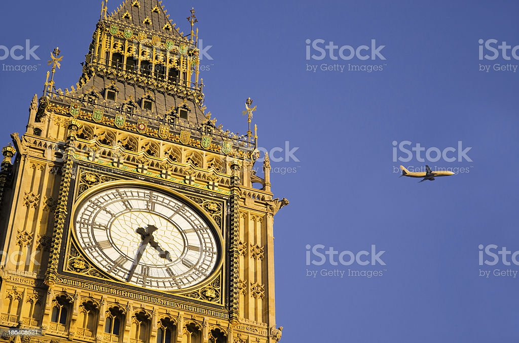 Big Ben clock tower with an airplane flying by royalty-free stock photo