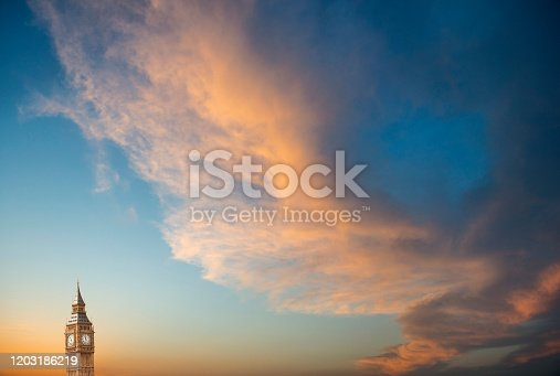 Big Ben in London at dusk. Large view of sky with clouds at sunset