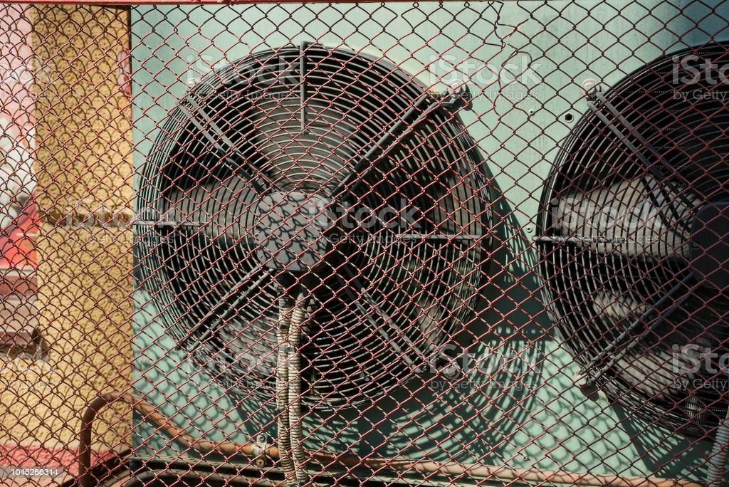 big black industrial fan on the wall behind a gray iron grating