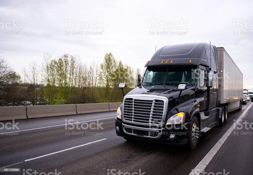 Big black modern semi truck rig trailer traffic on highway stock photo