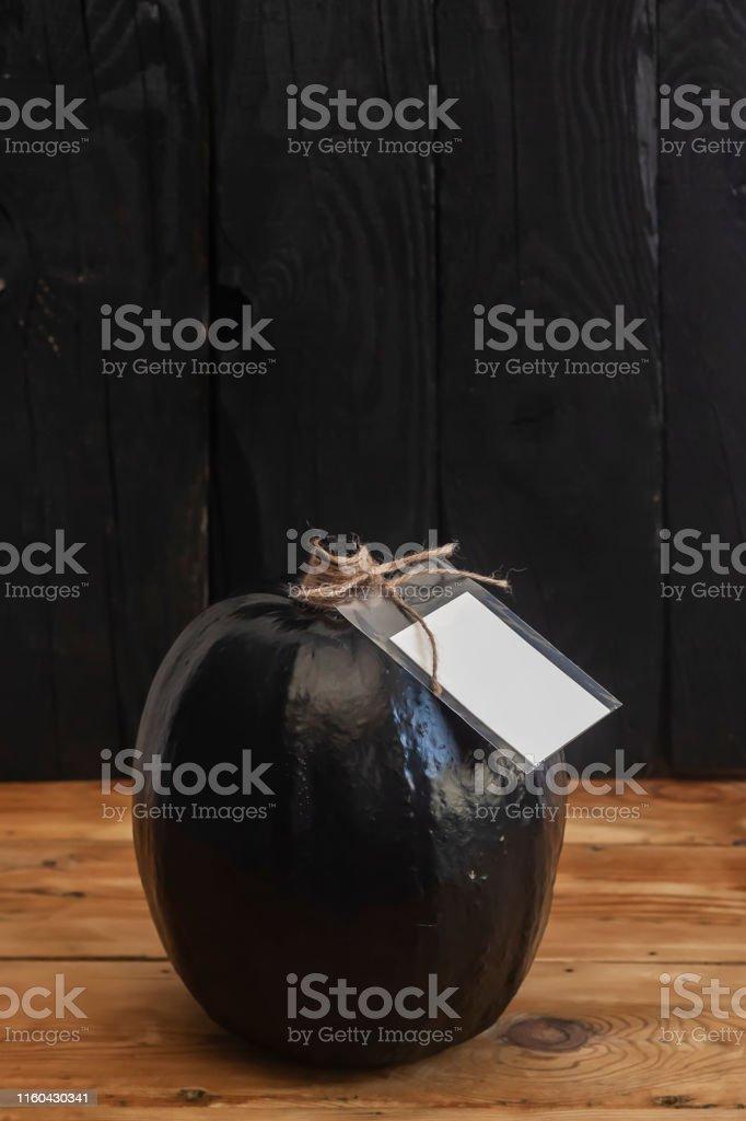 A big black pumpkin with an empty white tag. Autumn pumpkin decorated...