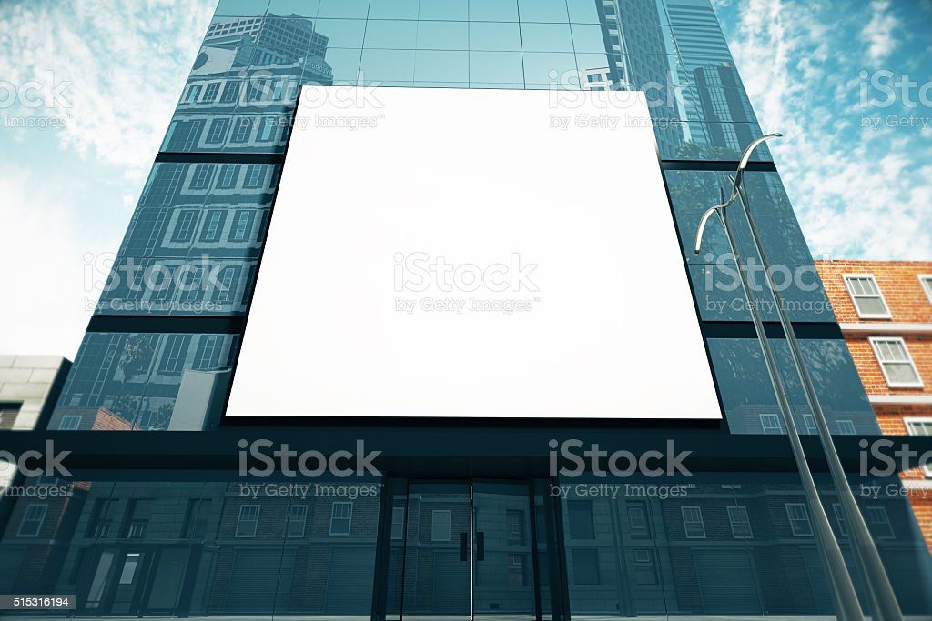 Big blank billboard on glassy business center at sunny day stock photo
