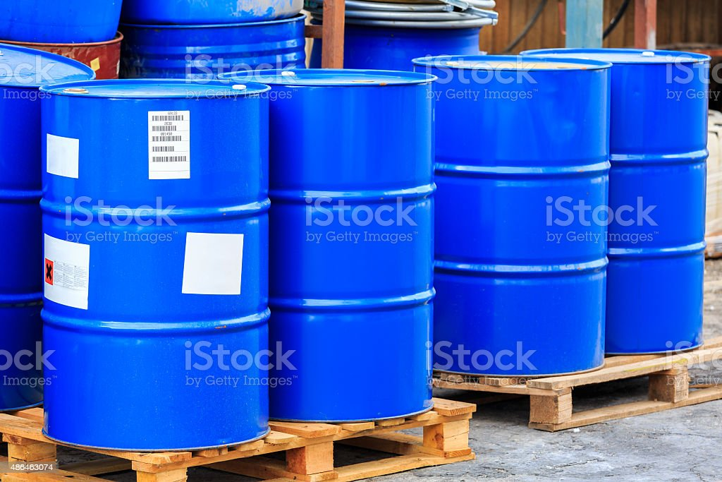 Big blue barrels on wooden pallets stock photo