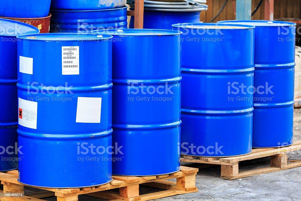 Big blue barrels on wooden pallets stock photo