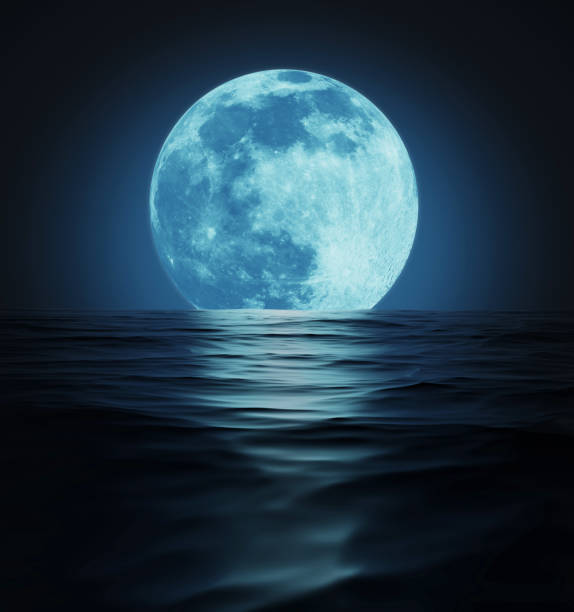 Big Blue Moon Reflected in Dark Water Surface stock photo
