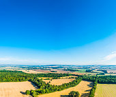 Big blue summer skies above an aerial view over picturesque patchwork landscape of green pasture, meadows, farm crops and leafy woodland amongst the rolling hills and quiet valleys of this picturesque rural landscape. ProPhoto RGB profile for maximum color fidelity and gamut.