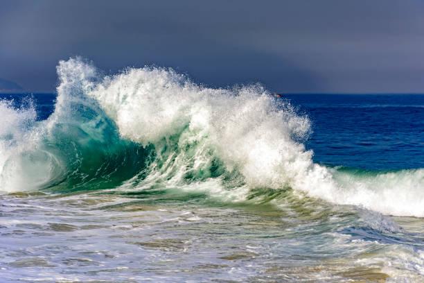 Big blue wave breaking on Ipanema beach stock photo
