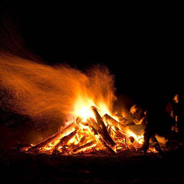 großes lagerfeuer und feuerwehrleute - osterfeuer stock-fotos und bilder