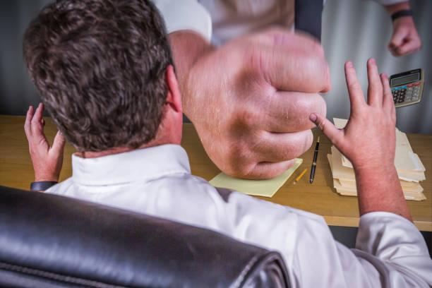 Big Boss Fist Slamming Down on Male Worker Desk - Work Stress Pressure Series. stock photo