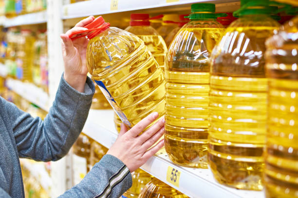 Big bottle of oil in hand buyer at grocery stock photo