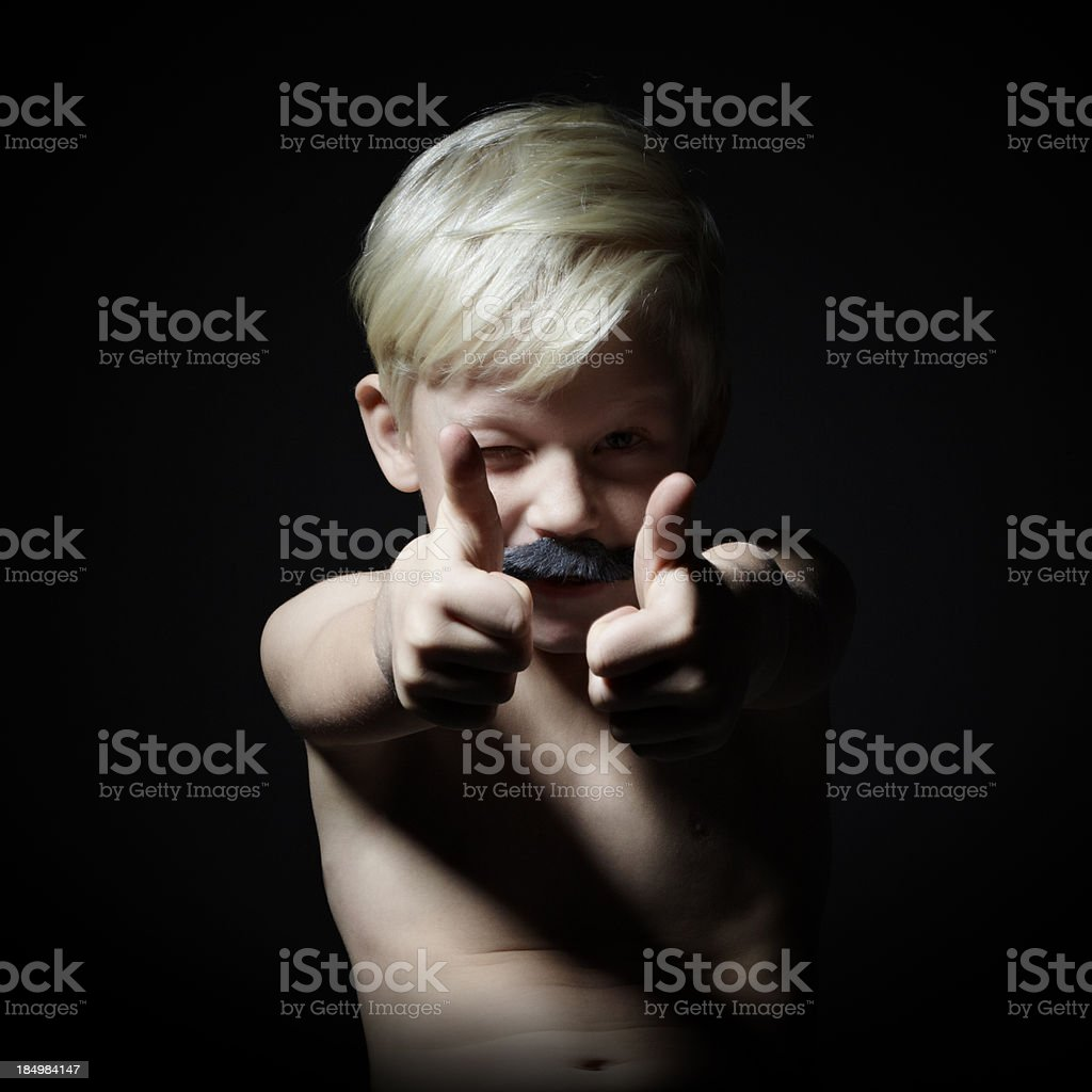 Little boy - with a beard - looking at camera and making thumbs up