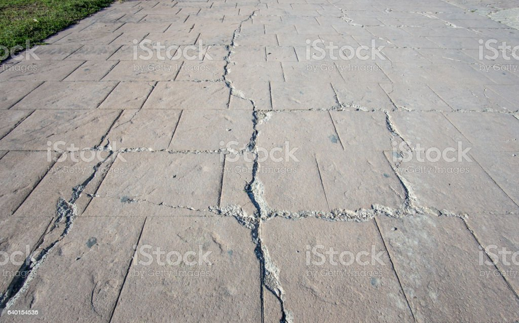 big break on damaged stamped concrete pavement outdoor, appearance colors stock photo