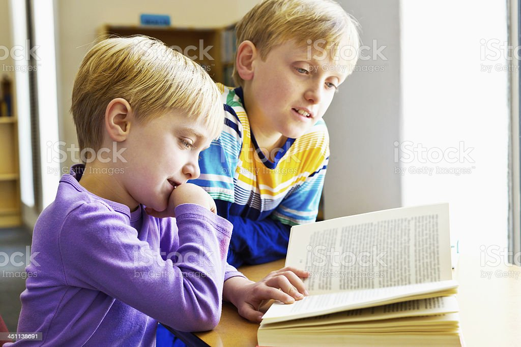 Big brother helps little sister with her reading in library stock photo