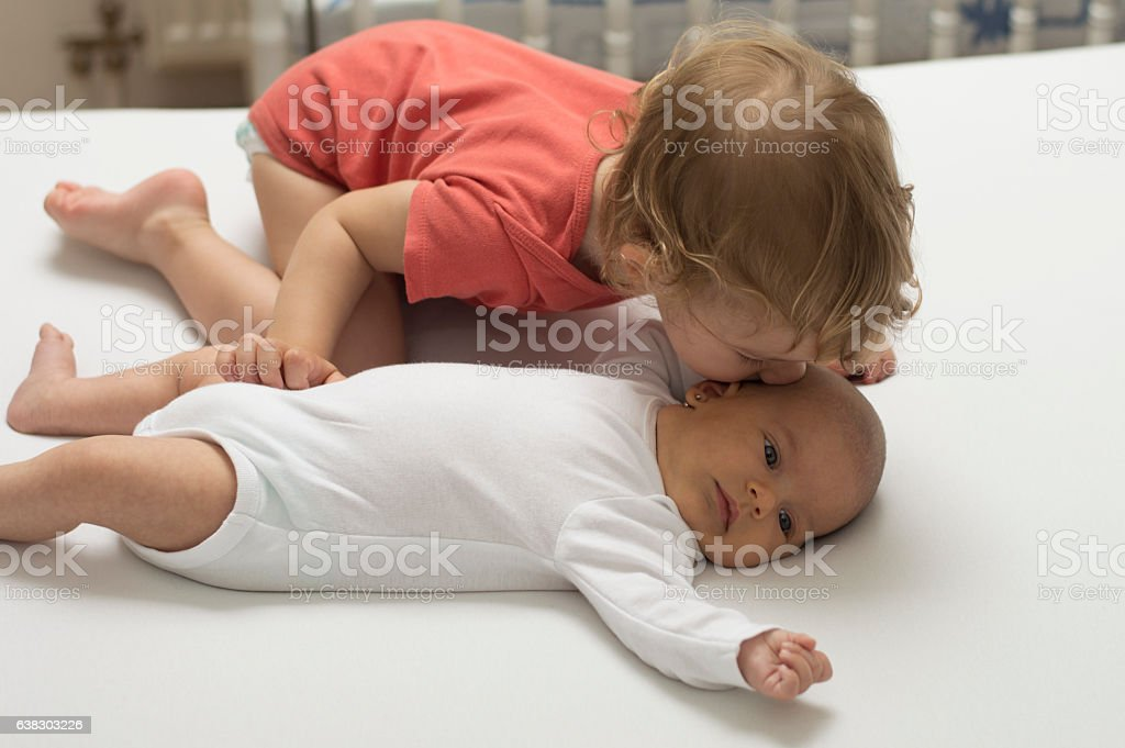Big brother kissing a newborn sister with love ストックフォト