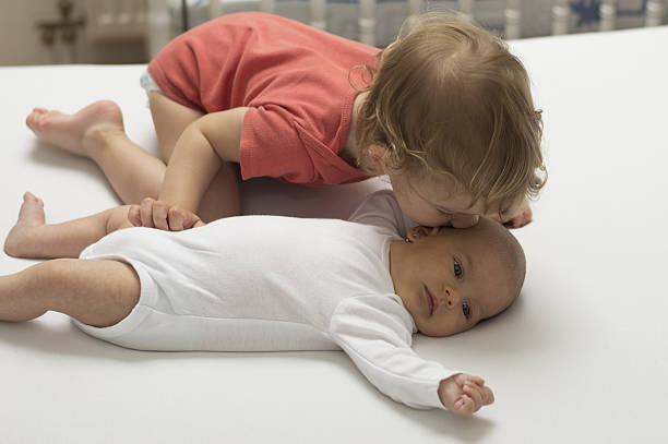 Big brother kissing a newborn sister with love stock photo