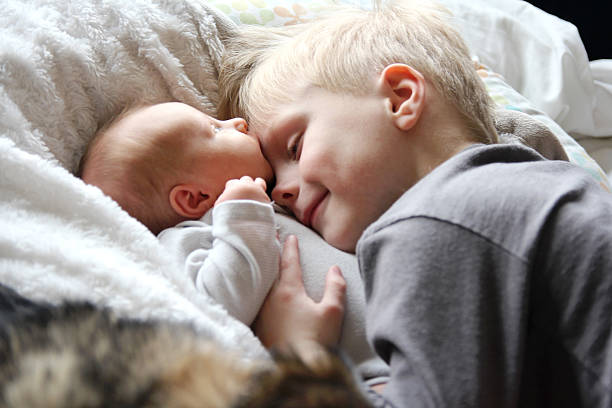 Big Brother Looking at Newborn Baby with Love A 5 year old big brother is hugging, smiling, and looking at his newborn baby sister as they sunggle in bed. brother stock pictures, royalty-free photos & images