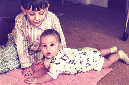Vintage photo of a boy with her baby sister on the floor at home.