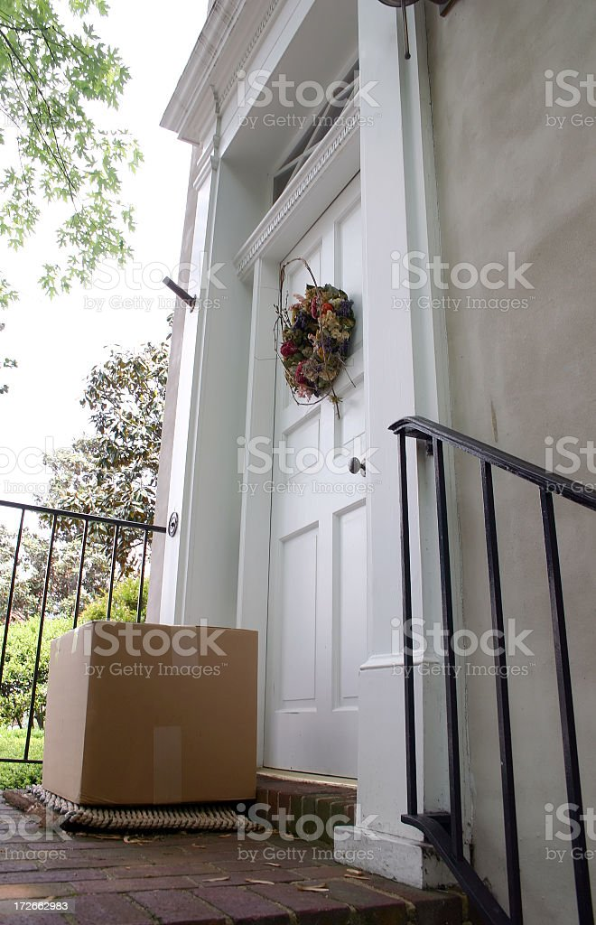A big brown box being delivered in the door step stock photo