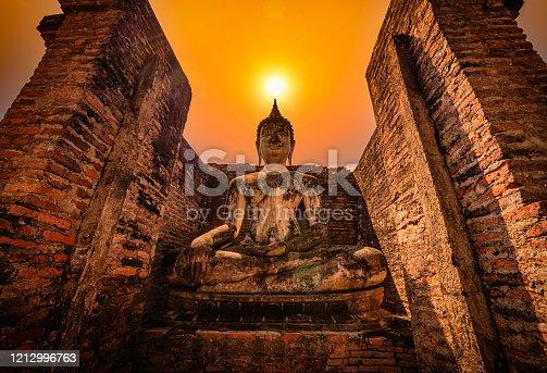 Big Buddha at sunset in Wat Mahathat temple, Sukhothai Historical Park, Thailand.