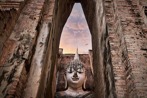 Big buddha sculpture in historical of sukhothai in wat sri chum with twilight skyline background