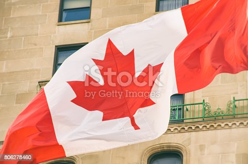 istock Big Canada flag waving in the wind with a wall in the background 806278460