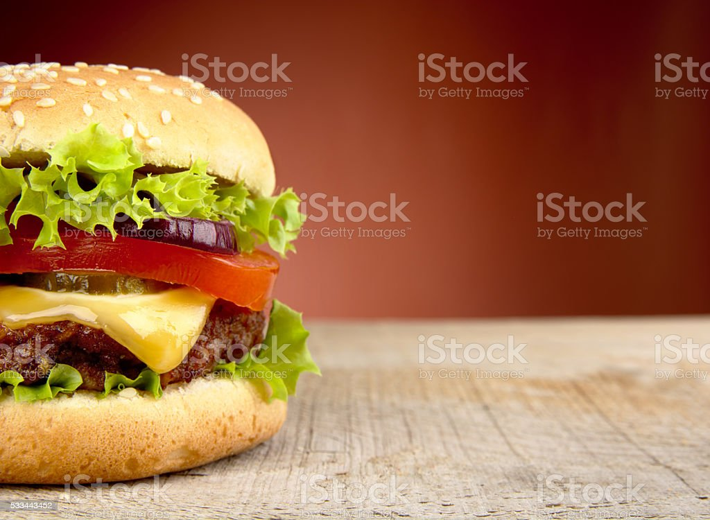 Big cheeseburger cropped on red background stock photo