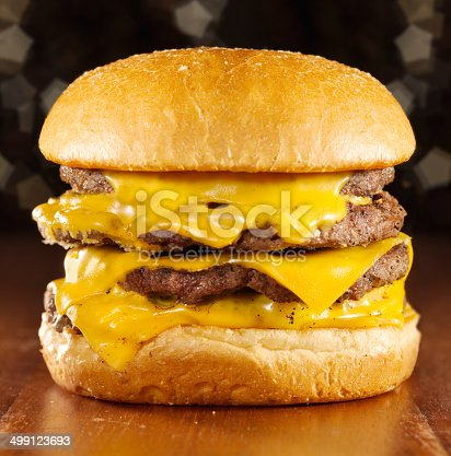 big cheeseburger with melted cheese shot with glitterly background and selective focus.