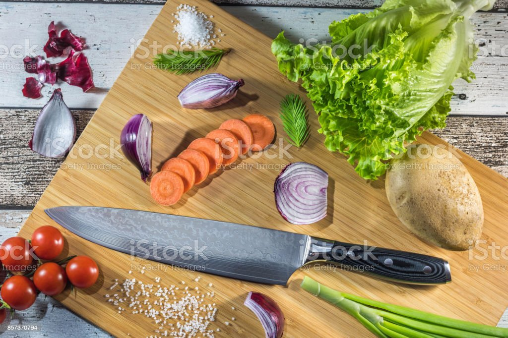 Big chef knife with healthy food - vegetables, onion, salad, potato placed on a cutting board with wood background top view stock photo
