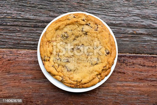 A large chocolate chip cookie on a white plate on top of a rustic wooden table