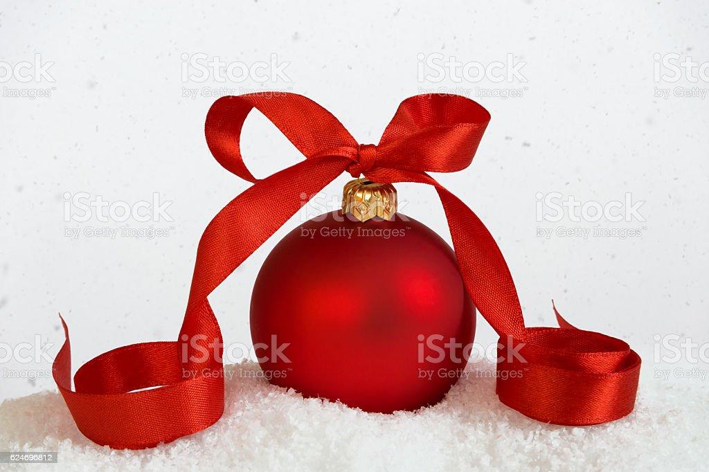 big christmas ball with ribbon falling snow stock photo