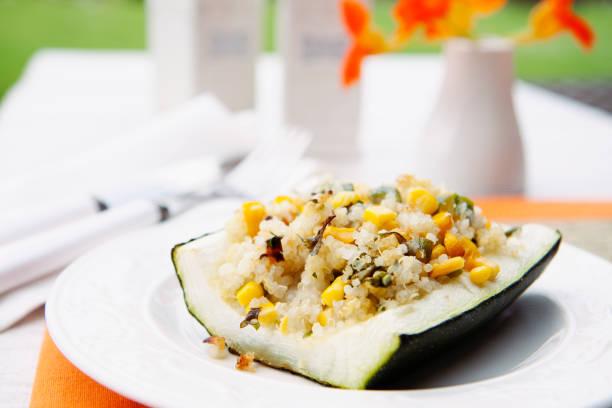 großes stück eine zucchini mit zwiebeln, mais, quinoa und spinat gefüllt und im ofen gebacken. heu-diät, gesunde ernährung rezept. - gefüllte zucchini vegetarisch stock-fotos und bilder