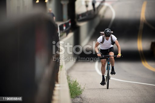 A male bicycle messenger rides in a designated bicycle lane on a city street on his way to make a delivery. He is riding a fixed-gear or one-speed bicycle and wears a courier backpack. He carries his bicycle lock key on his left wrist.