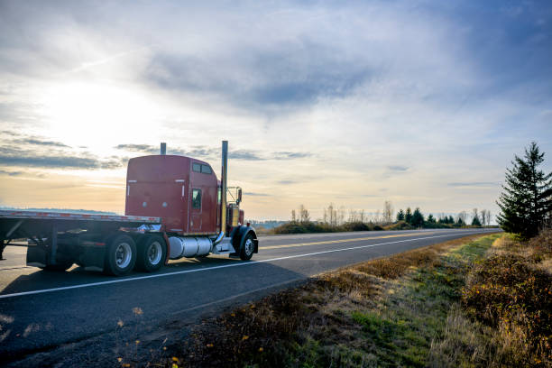 Big classic rig red semi truck with flat bed semi trailer running on the evening road with sunset stock photo