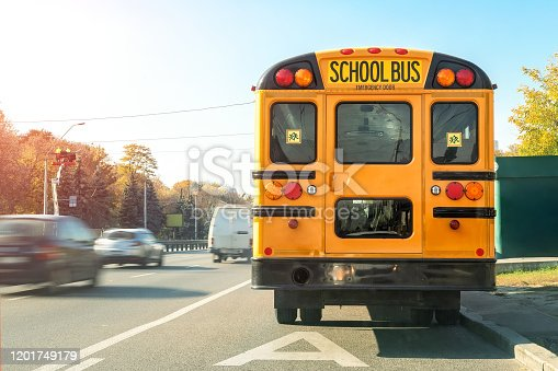 Big classic vintage american yellow schoolbus standing on a bus lane at highway and waiting pupils and children for school trip road. School bus transport back door view on route bright morning time.