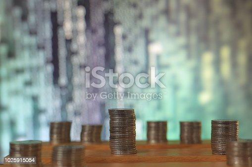 istock big coin piles in front of out of focus computer screen displayed blue green code matrix. online saving innovation idea. 1025915054