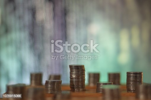 istock big coin piles in front of out of focus computer screen displayed blue green code matrix. online saving innovation idea. 1025915066