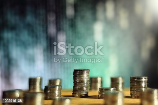 istock big coin piles in front of out of focus computer screen displayed blue green code matrix. online saving innovation idea. 1025915108