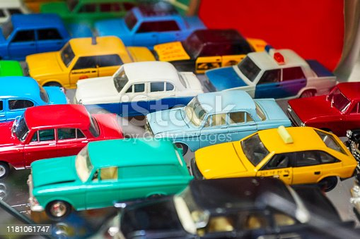 Big collection of retro car models on the shelf. Miniatures of colorful vintage vehicles in the shop. Selective focus.