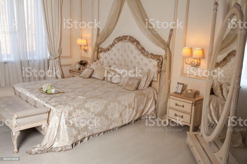 Big comfortable double bed in elegant classic bedroom stock photo